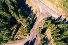 Vertical aerial view of a forest path leading to an asphalted country road stock photography