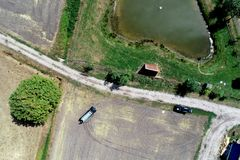 Vertical aerial view over a path next to a harvested field and a meadow with a small stable in front of a pond for fishing.  royalty free stock photo
