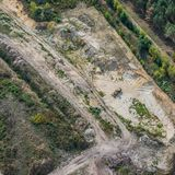 Vertical aerial view of a sand quarry in the heath with a wheel loader, flight with a gyrocopter royalty free stock photography
