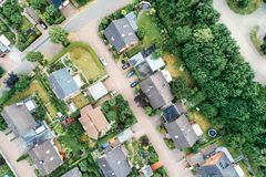 Vertical aerial view of a suburban settlement in Germany with detached houses, close neighbourhood and gardens in front of the hou. Ses, drone shot stock photo