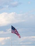 Vertical American Flag. Vertical image of an American flag against a light blue sky with gray and white cumulus clouds. The flag is unfurled in the wind. Image Royalty Free Stock Photography