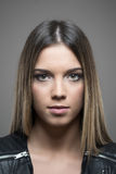 Vertical atmospheric portrait of young beauty with ombre hairstyle looking at camera. Over gray studio background Royalty Free Stock Photography