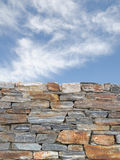 Vertical background with rough stone wall and blue cloudy sky Stock Photo