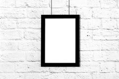 Vertical black photo frame hanging on brick wall. Mockup with copy space. Vertical black photo frame hanging on brick wall. Mockup with copy space stock photos