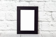 Vertical black photo frame on wooden table. Mockup with copy space.  royalty free stock images