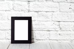 Vertical black photo frame on wooden table. Mockup with copy space stock photography