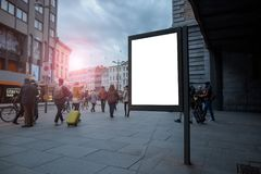 Vertical blank billboard in the city center with Mock up. The layout is located in a crowded street with people. Vertical blank billboard in the city center stock photos