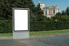 Vertical blank glowing billboard on the city street. In the background buildings and road with cars. Mock up. stock images