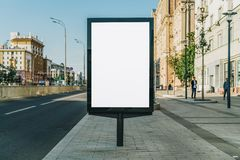 Vertical blank glowing billboard on the city street. In the background buildings and road with cars. Mock up. Stock Photo