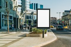 Vertical blank glowing billboard on the city street. In the background buildings and road with cars. Mock up. royalty free stock photography