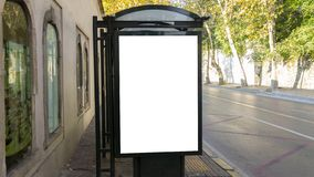 Vertical blank white billboard at bus stop on city old street royalty free stock photos
