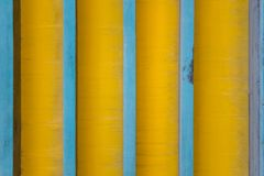 Vertical blue lines on a dirty yellow background with shadows. rough surface texture stock photography