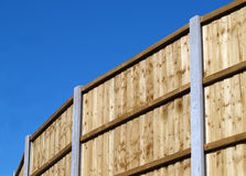 Vertical board fence panel. S with concrete posts against blue sky stock photography