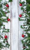 Vertical borders of snowy Christmas red ornaments and candy cane. Snowy Christmas tree branches, candy canes and red ornaments forming vertical borders on rustic royalty free stock image