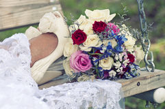 Bride on Swing with Shoes & Bouquet. Bride on a swing with her legs extended for a shot of her shoes and the bridal bouquet Royalty Free Stock Photo