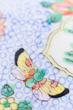 Vertical butterfly. Hand drawn decorated chinese Porcelain decorated with a Butterfly and blue circles witn lines and green color, close up stock photos