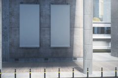 Vertical canvas on concrete building. Two blank white vertical canvas hanging on concrete building. Daytime. Ad concept. Mock up, 3D Rendering Royalty Free Stock Photo