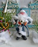 Retro picture of plasticine Father Frost, decorated New Year tree and beautiful shutters in the background. Vertical Christmas photo of plasticine small Santa Stock Image