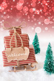 Vertical Christmas Sleigh On Red Background, Text Welcome. Vertical Image Of Sleigh Or Sled With Christmas Gifts Or Presents. Snowy Scenery With Snow And Trees stock image