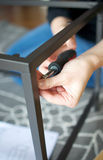 Vertical close up of hands screwing together metal furniture pieces Royalty Free Stock Photo