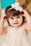 Vertical close up indoor portrait of cute happy baby girl playing with dressy white headband Royalty Free Stock Photos