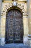 Wooden door of St. Publius Parish Church in Floriana, Malta. Vertical close-up photo of St. Publius Parish Church- wooden door in Floriana, Malta Royalty Free Stock Image