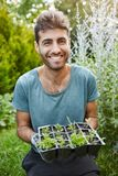 Vertical close up portrait of mature good-looking bearded gardener in blue t-shirt smiling in camera, holding pot with. Planted sprouts in hands Stock Images