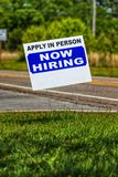 Now Hiring Sign With Copy Space. Vertical close-up shot of a Now Hiring Sign with copy space. Background is out of focus stock photography