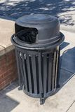 Outdoor Trash Receptable. Vertical close-up shot of an outdoor trash receptacle sitting on a sidewalk Stock Photo