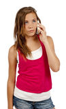 Teenager On Mobile Phone Or Cell Phone Looking Frustrated Isolated On White. Vertical close up shot of a young teenage girl listening on the phone and looking Royalty Free Stock Photos