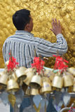 Vertical close up view of Pilgrim carefully pasting gold foils onto golden rock at the Kyaiktiyo Pagoda with row of small bells Stock Photography