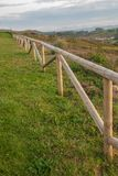 Vertical close-up of wooden fence in a green field. At sunset stock image