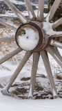 Vertical Close up of the wooden wheel of an old wagon against a snowy terrain in winter stock images