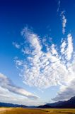 Vertical cloudscape. Vertical wide angle shot of a blue sky and distant mountains with coastal marshes in the foreground Royalty Free Stock Images