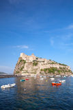 Vertical coastal landscape of Ischia port. With Aragonese Castle and anchored pleasure boats Stock Photo