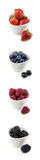 Vertical collection of berries in bowls. Strawberries, blueberries, raspberries and blackberries in white ceramic bowles on white background isolated Stock Photography