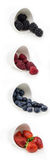 Vertical collection of berries in bowls. Strawberries, blueberries, raspberries and blackberries in white ceramic bowles on white background isolated Stock Images