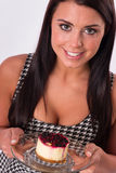 Vertical Composition Attractive Brunette Woman Eating Cheesecake. Beautiful woman smiles while eating cheesecake dessert Royalty Free Stock Images