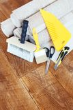 Vertical composition with some tools for wallpapering and rolls of wallpaper. On wooden floor Royalty Free Stock Photos