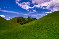 Conceptual view of a hill and sky with clouds. Vertical conceptual view of a hill and sky with clouds in the Gyeongju Tumuli Park stock photography