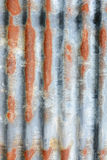 Vertical corrugated iron sheet with patches of rust Stock Photo