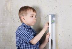 Vertical de medição do menino da parede pelo nível Imagens de Stock Royalty Free