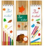 Vertical de nuevo a banderas de escuela con las herramientas de la escuela y las hojas de otoño en la superficie de madera Foto de archivo