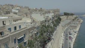 Vertical del vuelo del abejón para arriba a través de la calle vieja hermosa, cerca del mar en La Valeta, Malta Viejo, ventanas d metrajes