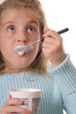 Vertical del yogur de la consumición de la chica joven que mira para arriba Imagen de archivo libre de regalías
