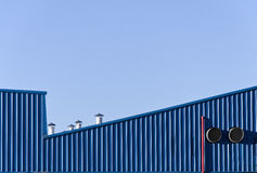 Vertical and diagonal. Blue painted wall chimneys and vents of a factory Royalty Free Stock Images