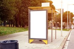 Vertical empty billboard placeholder on the city bus stop, information banner template, space for mockup layout. Vertical empty billboard placeholder on the stock photography