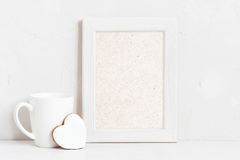 Vertical empty white wooden frame. Cup and cookie on the white background royalty free stock photo
