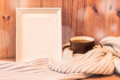 Vertical empty white wooden frame and mug with coffee. Wrapped in gray woolen scarf royalty free stock images