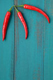 Vertical flat lay view of three hot red chili peppers Royalty Free Stock Photography